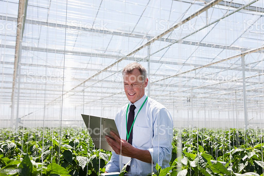 Businessman Holding on clipboard in greenhouse royalty-free stock photo