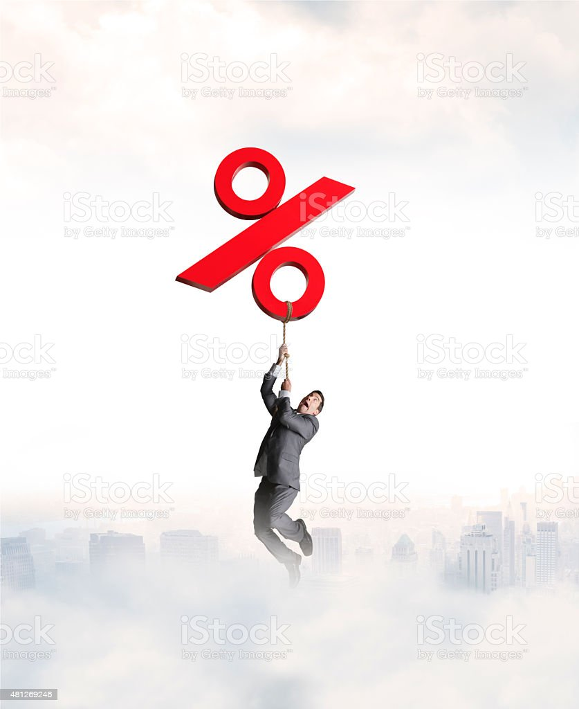 Businessman Holding On To Rising Red Percentage Sign stock photo