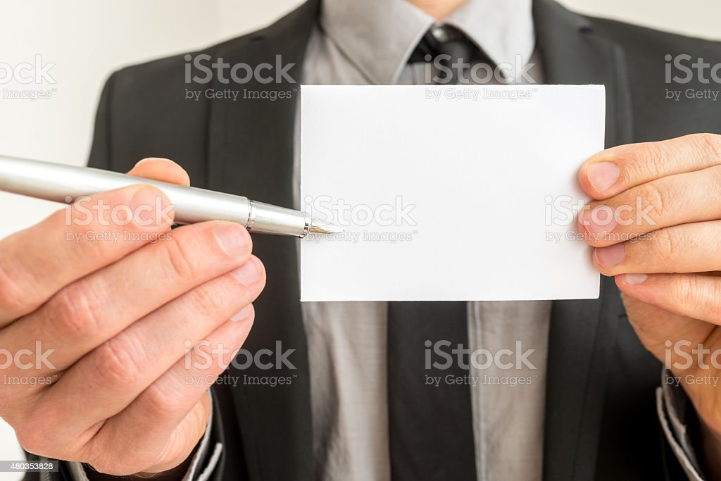 Businessman holding out a blank card and pen stock photo