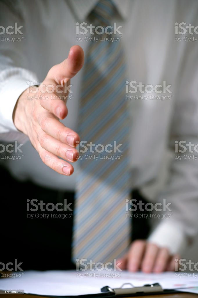 Businessman holding out hand in a motion to shake another's royalty-free stock photo