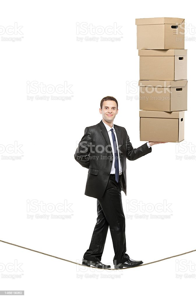 Businessman holding paper boxes and walking on a rope royalty-free stock photo