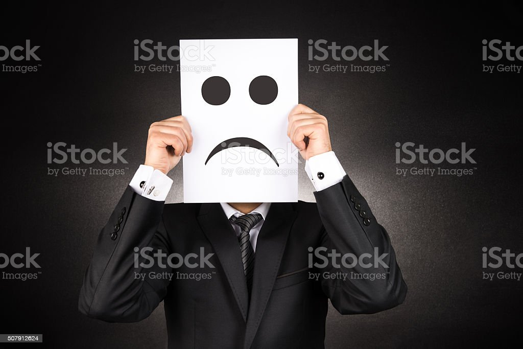 Businessman holding paper with sad emoji stock photo