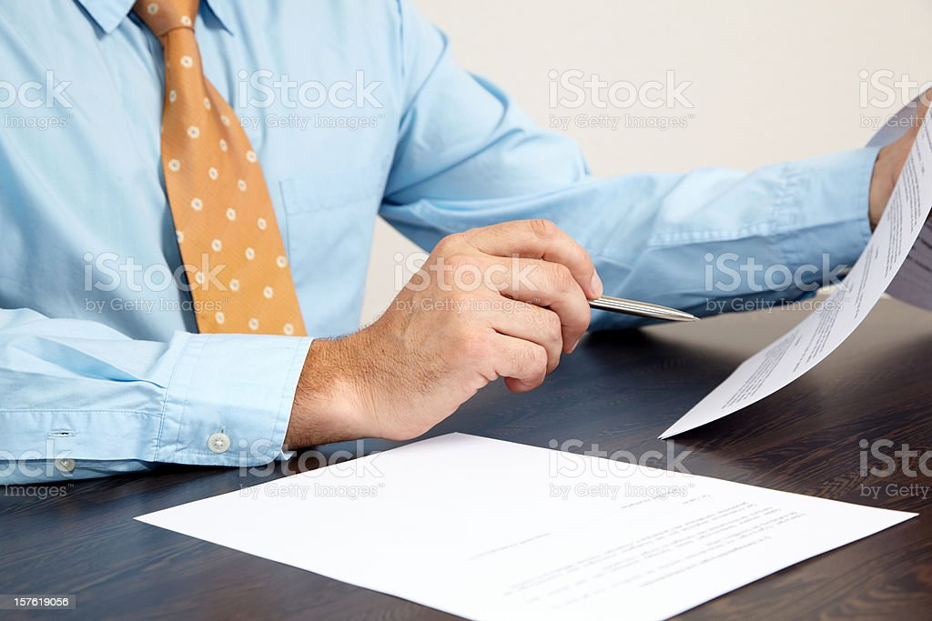 A businessman holding papers at a desk stock photo