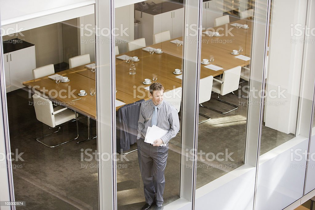 Businessman holding paperwork and looking out conference room window royalty-free stock photo