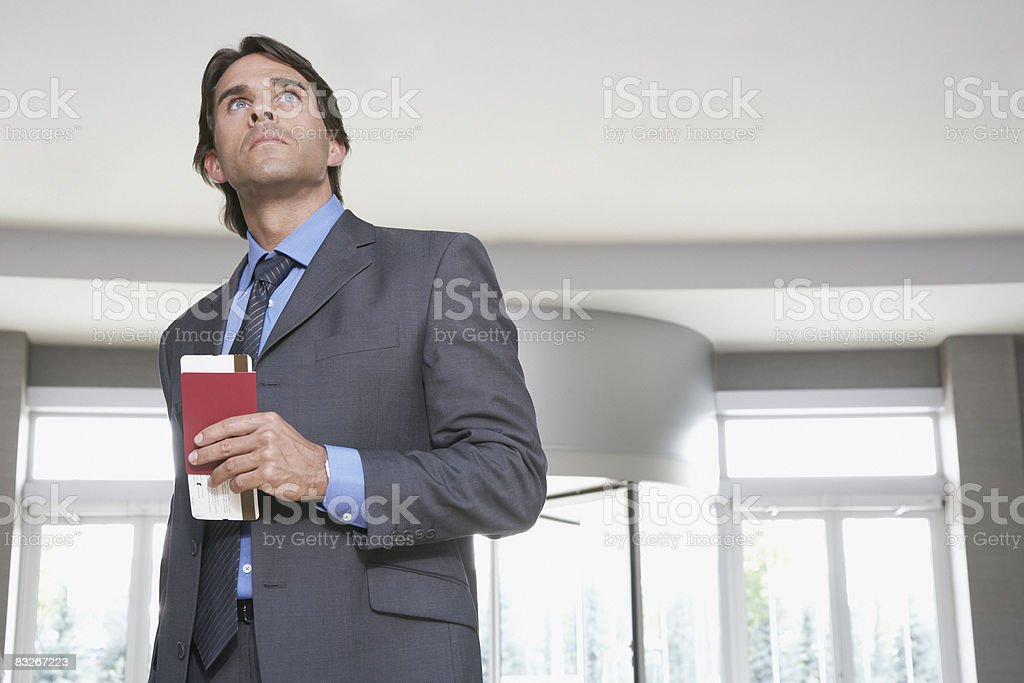 Businessman holding passport and airline ticket royalty-free stock photo