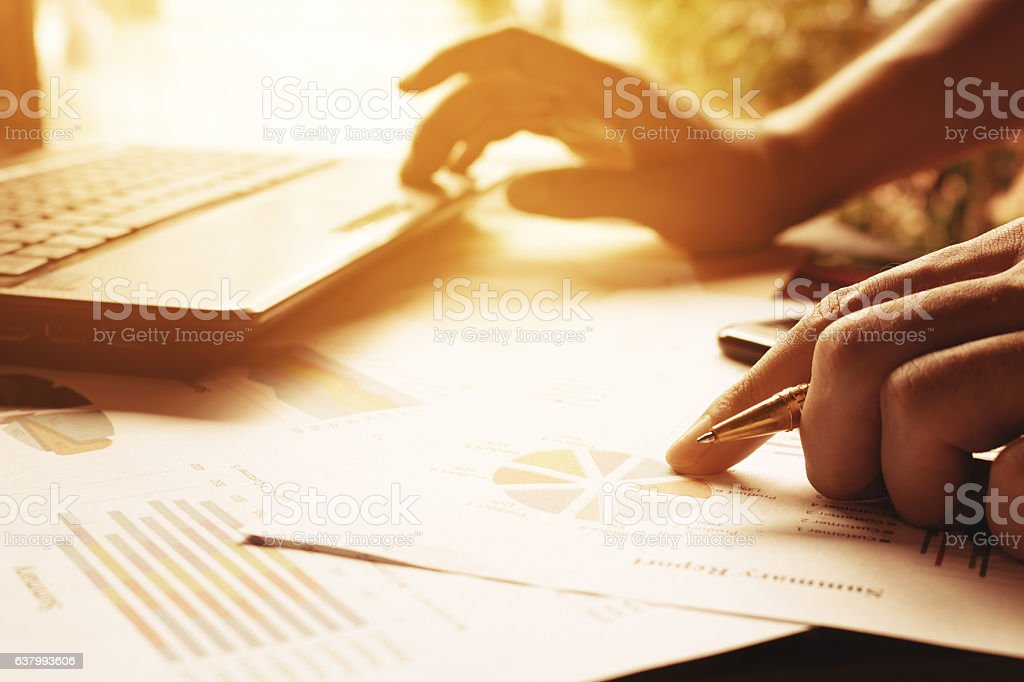 Businessman holding pen on charts and graph stock photo