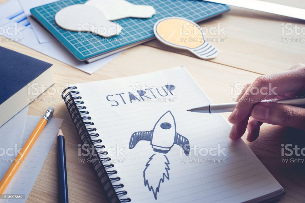 businessman holding pen with drawing startup text on notebook. stock photo