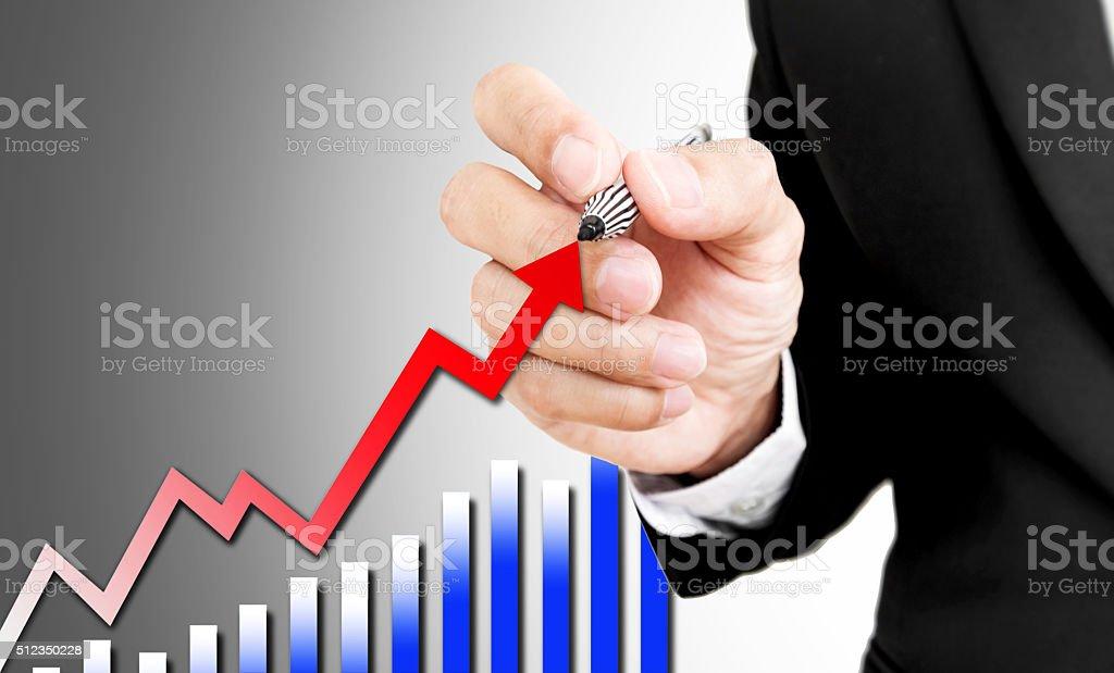 Businessman holding pen writing rising arrow and bar graph stock photo