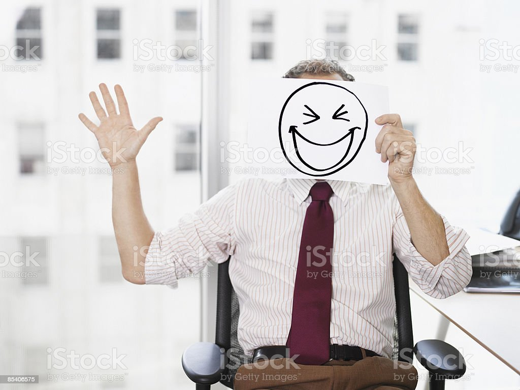 Businessman holding picture of laughing face stock photo
