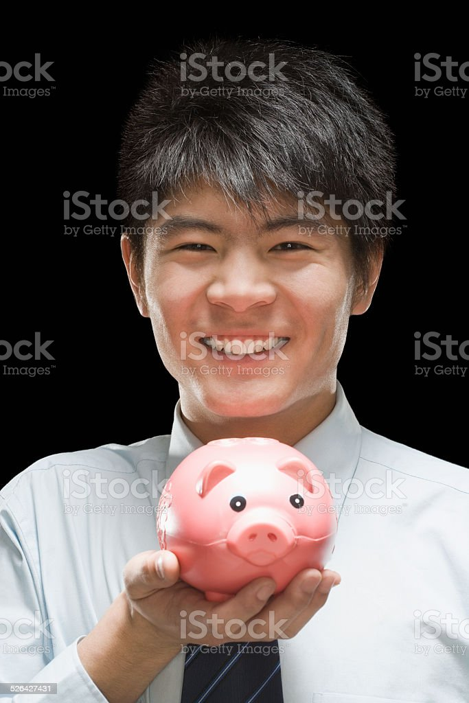 Businessman holding piggy bank, smiling, portrait stock photo