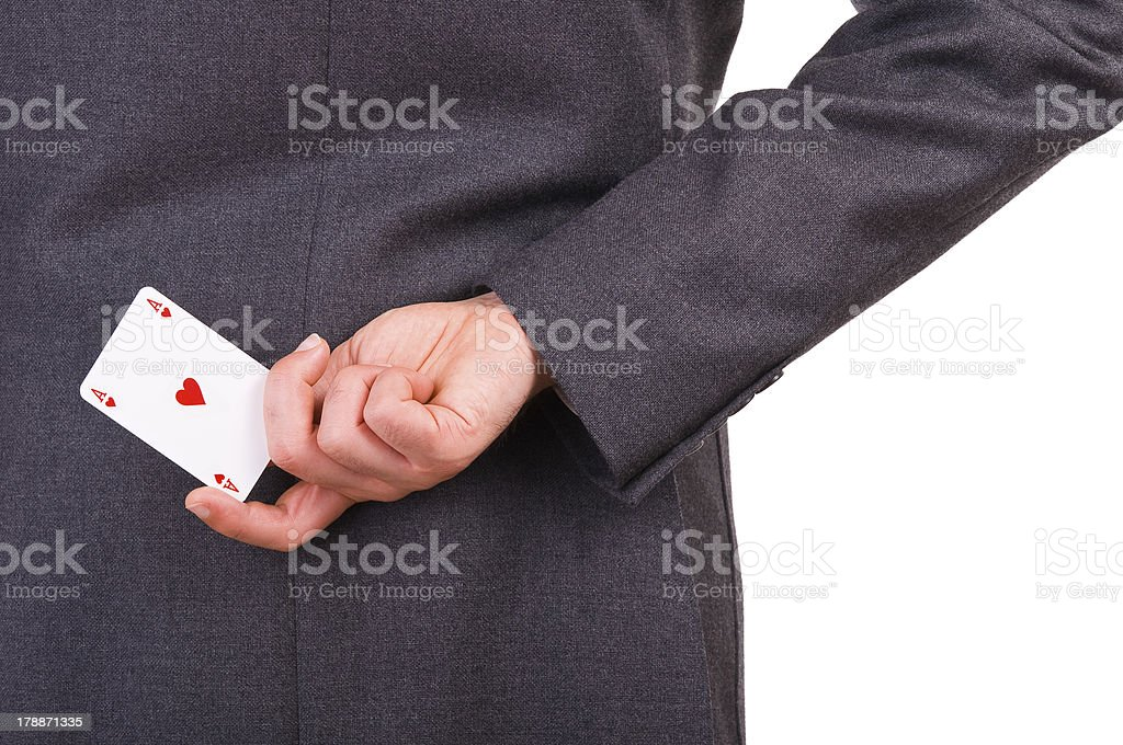 Businessman holding playing card behind his back. royalty-free stock photo