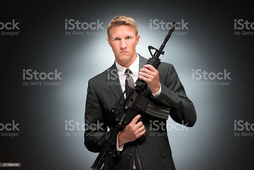 Businessman holding rifle stock photo