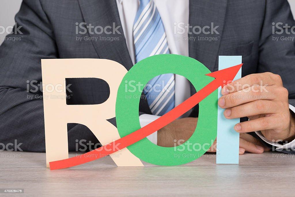 Businessman Holding ROI With Upward Moving Arrow stock photo