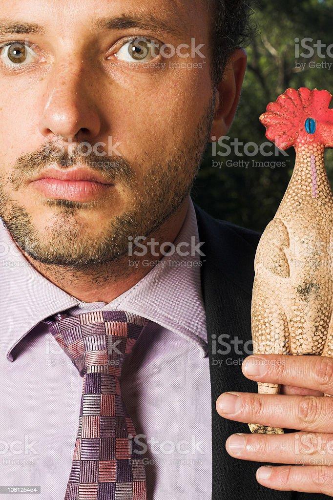 Businessman Holding Rubber Chicken stock photo