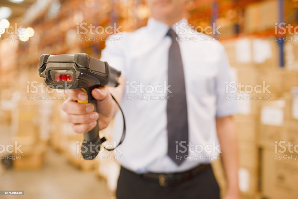 Businessman holding scanner in warehouse stock photo