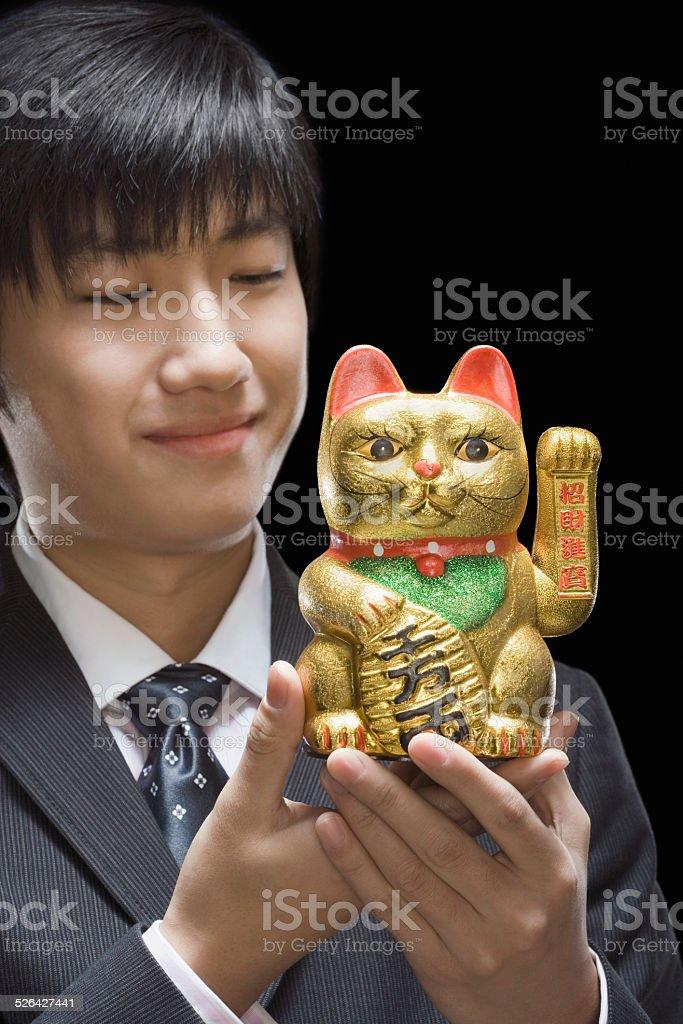 Businessman holding sculpture of traditional fortune cat Maneki Neko stock photo