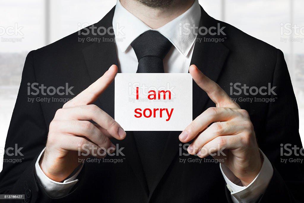 businessman holding sign i am sorry stock photo