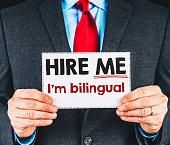 Businessman holding sign reading, I'm Bilingual