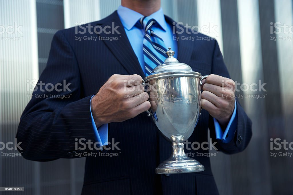 Businessman Holding Silver Trophy in front of Shiny Building royalty-free stock photo
