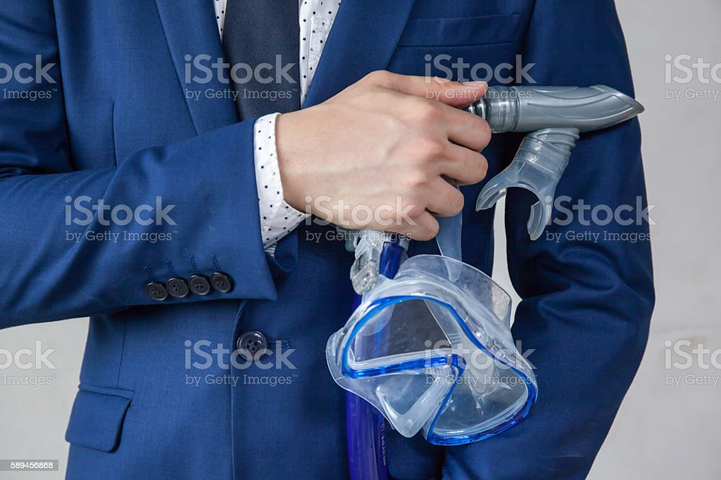 Businessman holding snorkeling goggle in white background stock photo