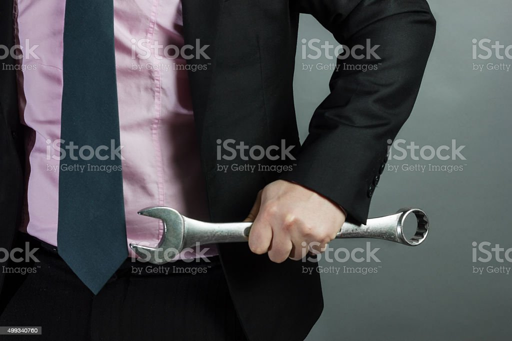 businessman holding spanner in hand stock photo