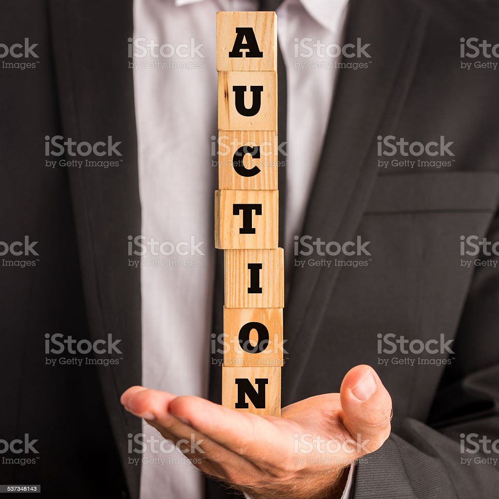 Businessman holding stacked blocks reading Auction stock photo
