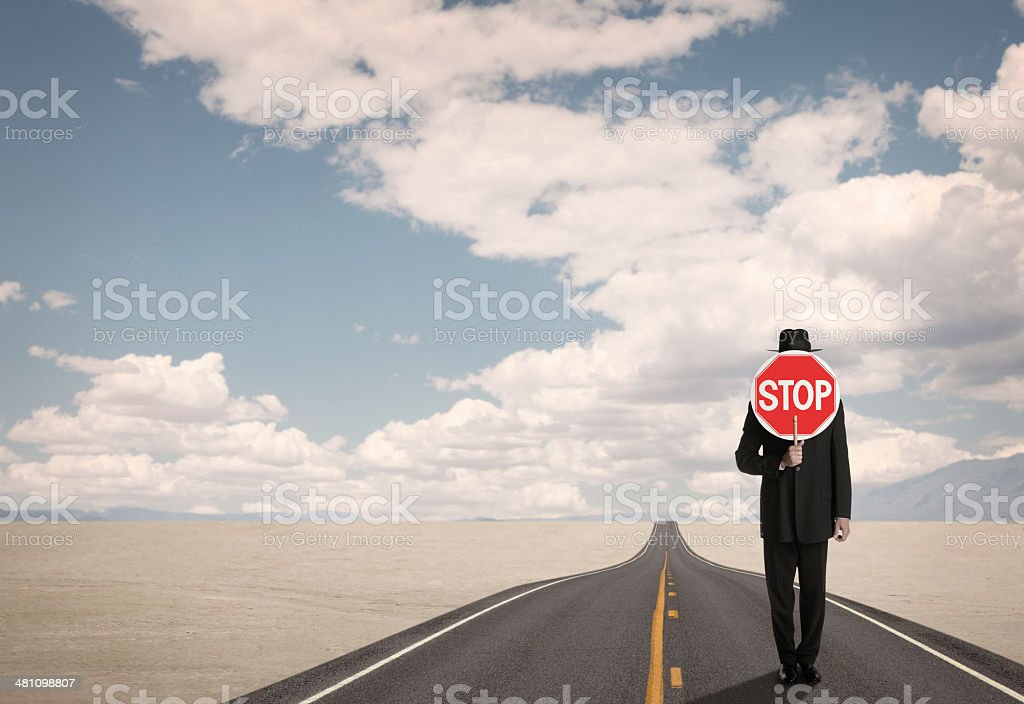 Businessman holding stop sign on remote road in the desert stock photo