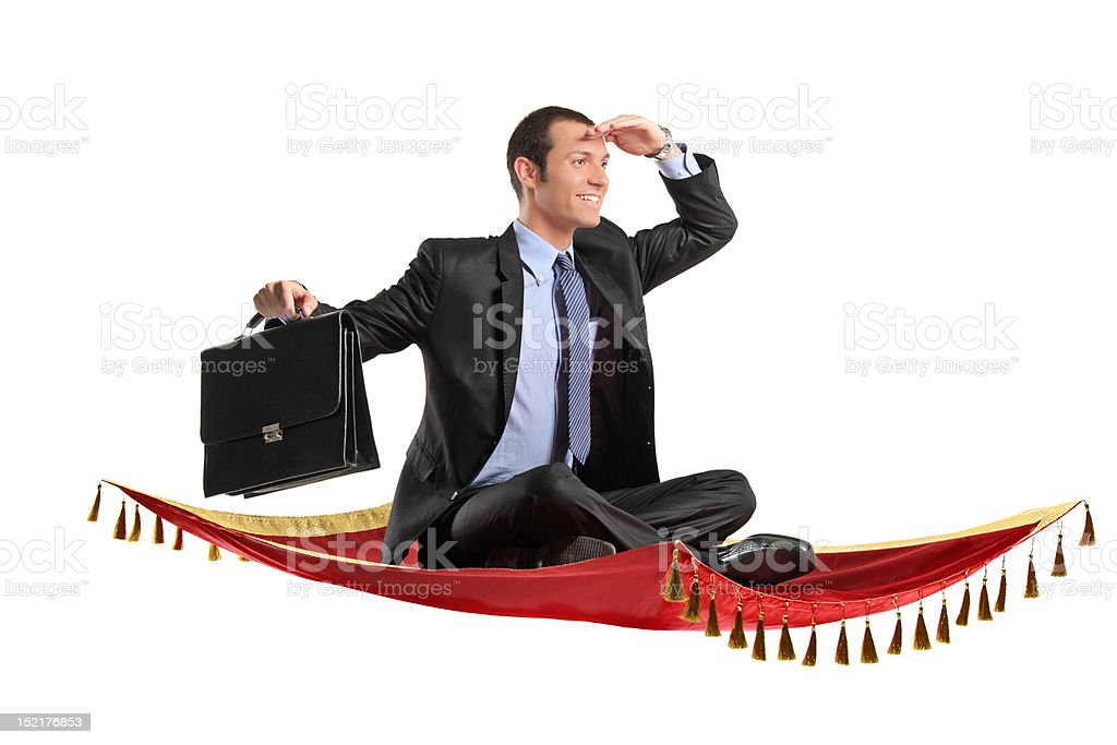 Businessman holding suitcase while flying on a carpet stock photo