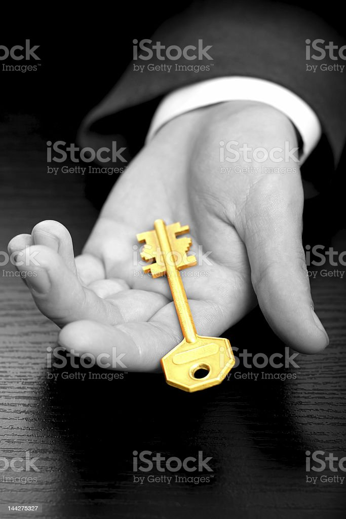 Businessman holding the business gold key stock photo