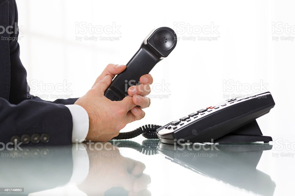 Businessman holding the receiver of a black landline telephone stock photo