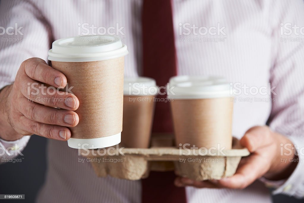 Businessman Holding Tray Of Takeaway Coffee stock photo