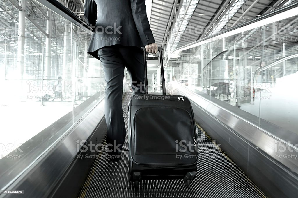 Businessman holding trolley bag going up on the escalator stock photo