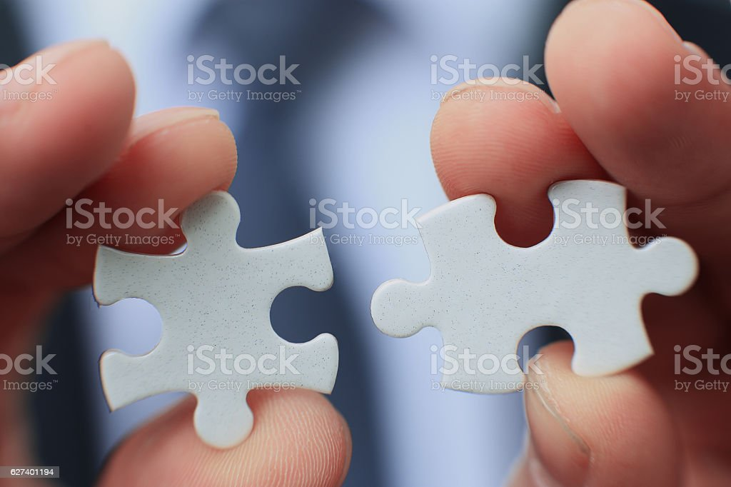 Businessman holding two blank white puzzle pieces in his hands stock photo