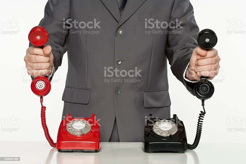 Businessman holding two different coloured vintage phone receivers royalty-free stock photo