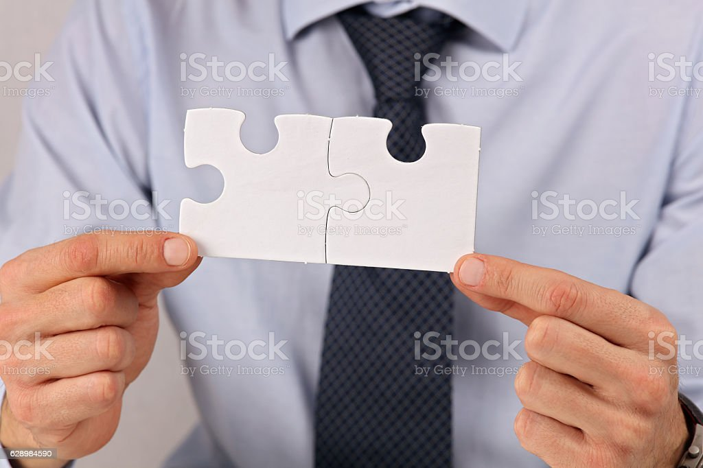 Businessman holding two pieces of a blank puzzle stock photo