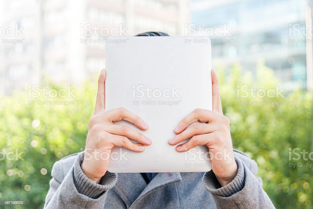 Businessman holding up a tablet in front of his face stock photo