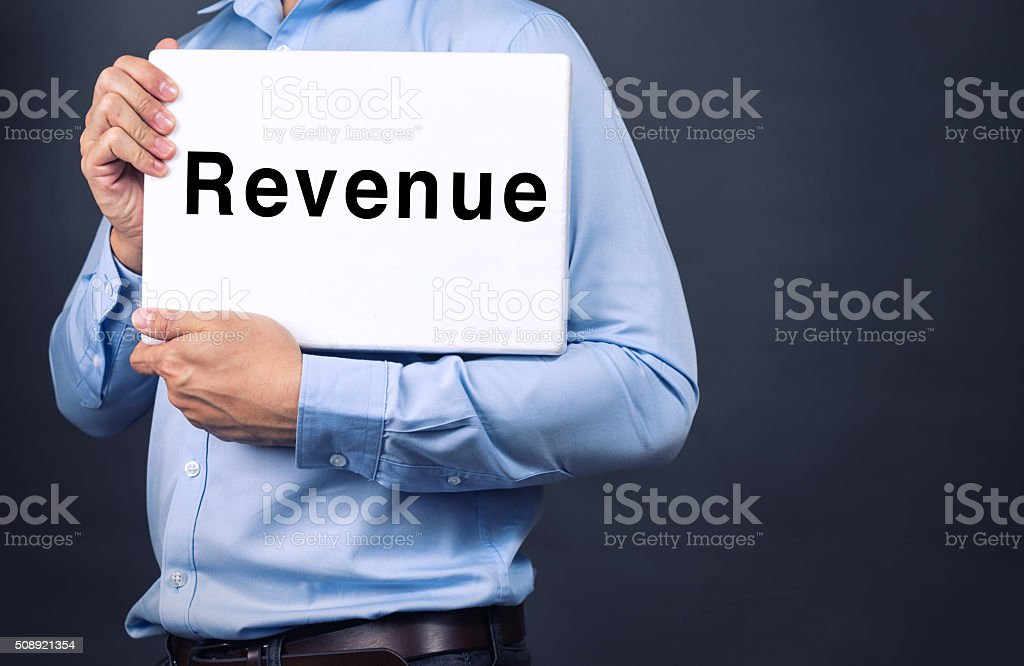 Businessman holding white board with REVENUE WORD stock photo
