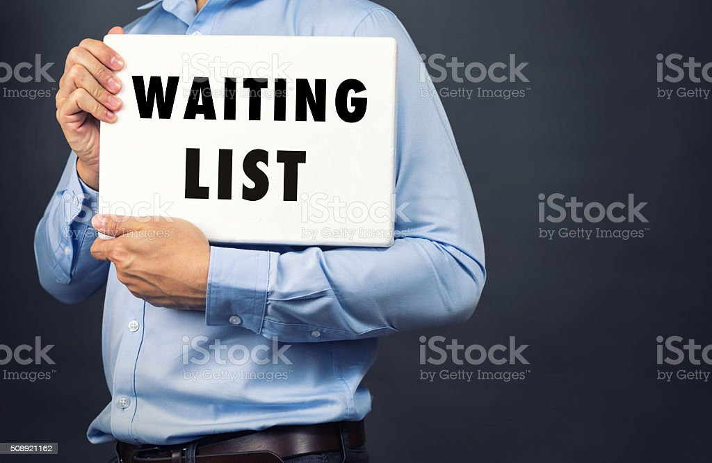 Businessman holding white board with WAITING LIST WORD stock photo