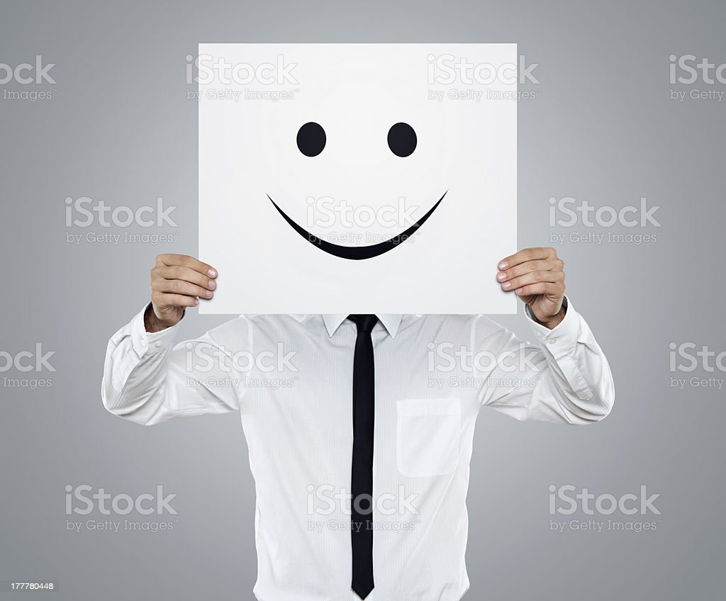 Businessman holding white card with emoticon on it stock photo
