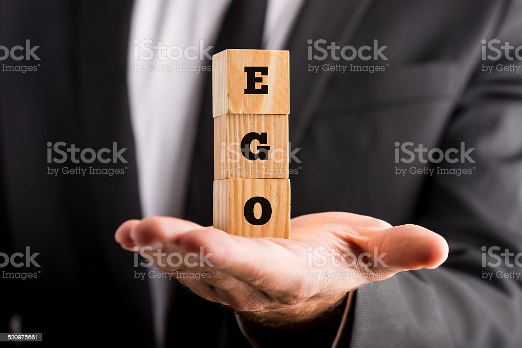 Businessman holding wooden alphabet blocks reading - Ego stock photo