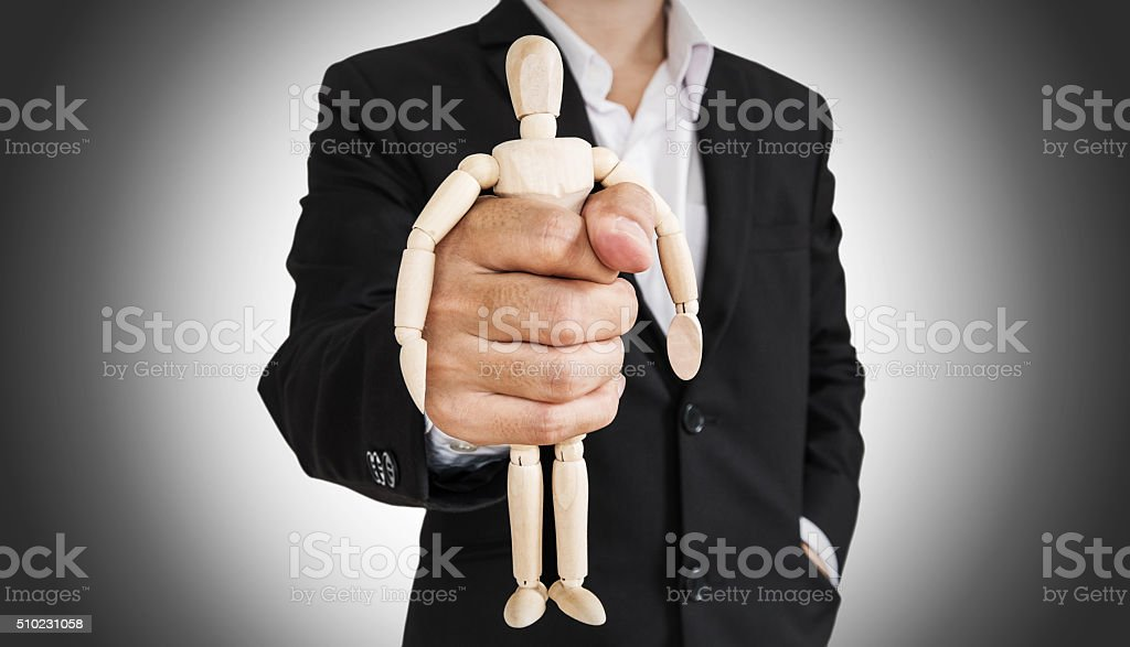 Businessman holding wooden figure, abstract concept stock photo