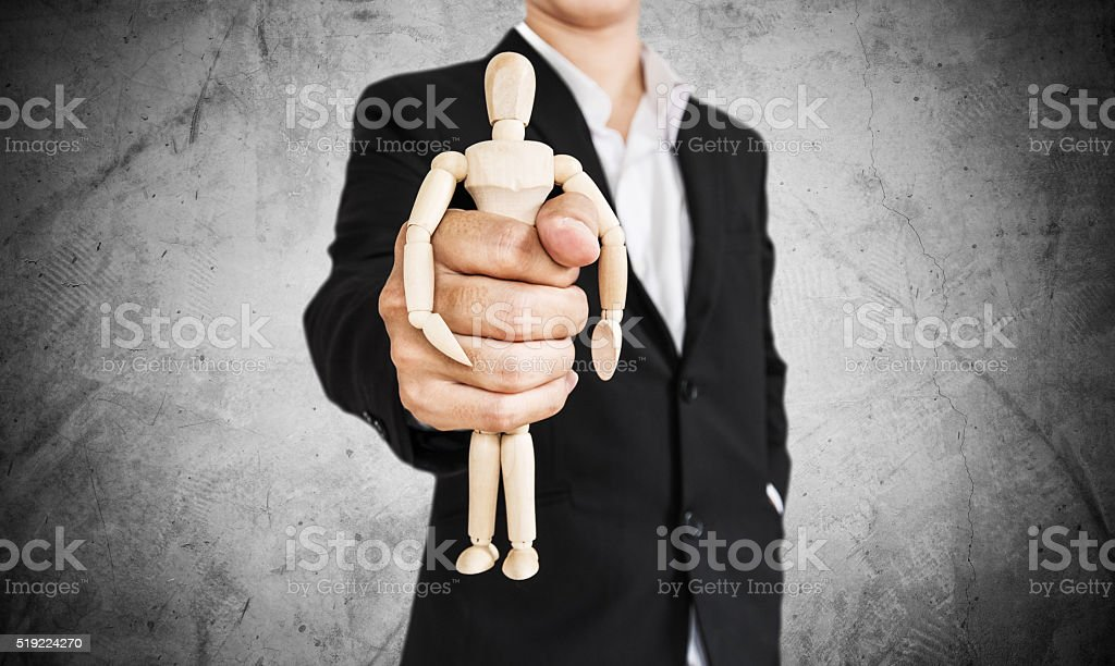Businessman holding wooden figure, on concrete texture background stock photo
