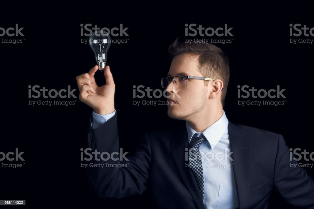 Businessman holds a burning light bulb at the tip of his finger. Man in a business suit looks at a light bulb located at his fingertip on a black background. stock photo