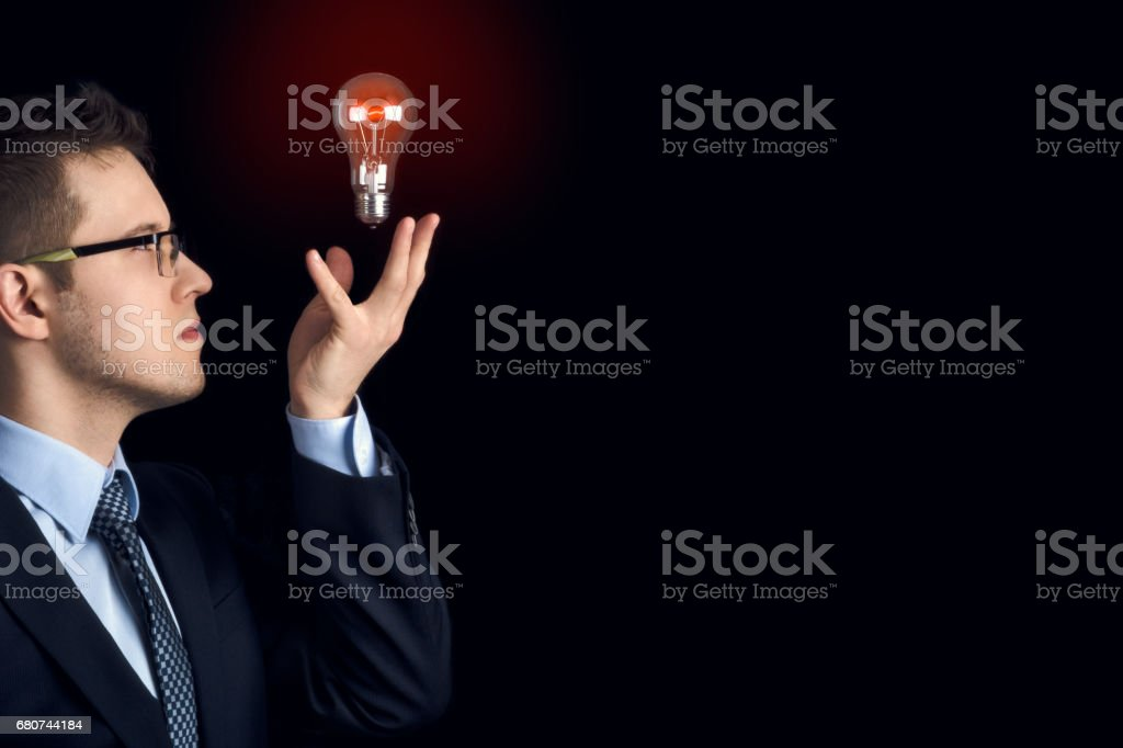 A businessman holds a burning light bulb in the air as a symbol of knowledge and ideas. stock photo