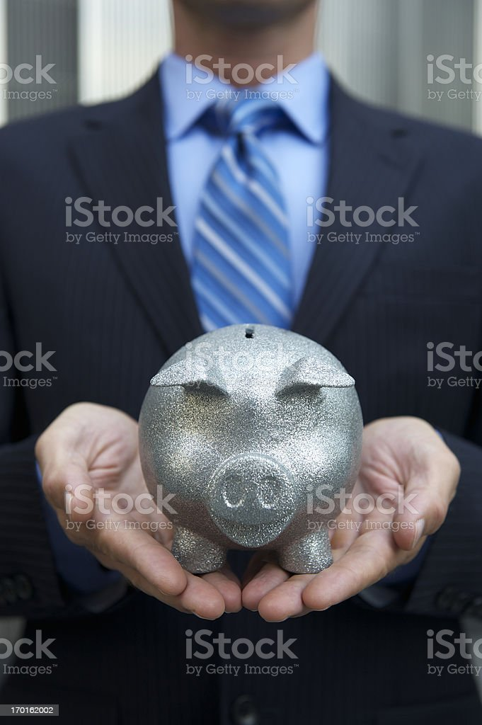 Businessman Holds a Shiny Silver Piggy Bank royalty-free stock photo