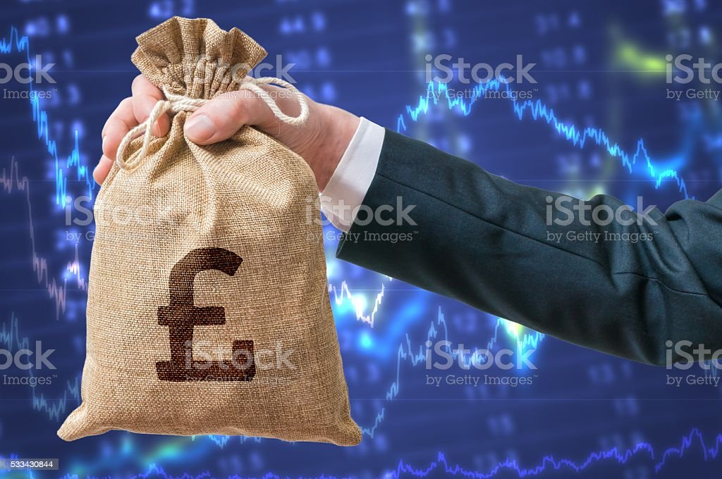 Businessman holds bag full of money with British pounds. stock photo