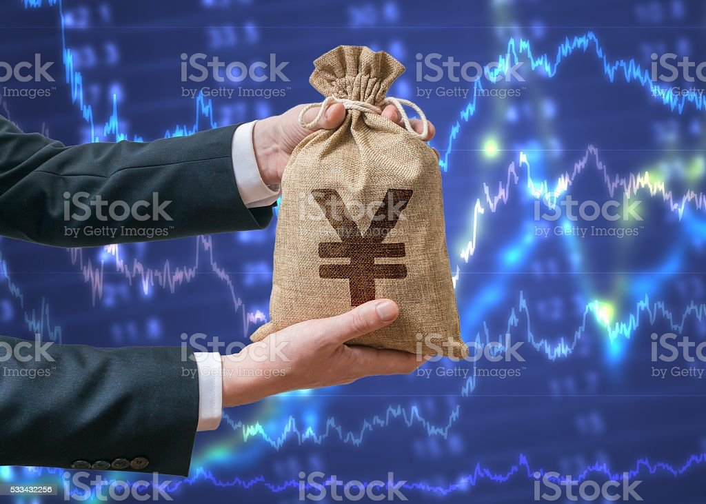 Businessman holds bag full of money with Yen sign. stock photo