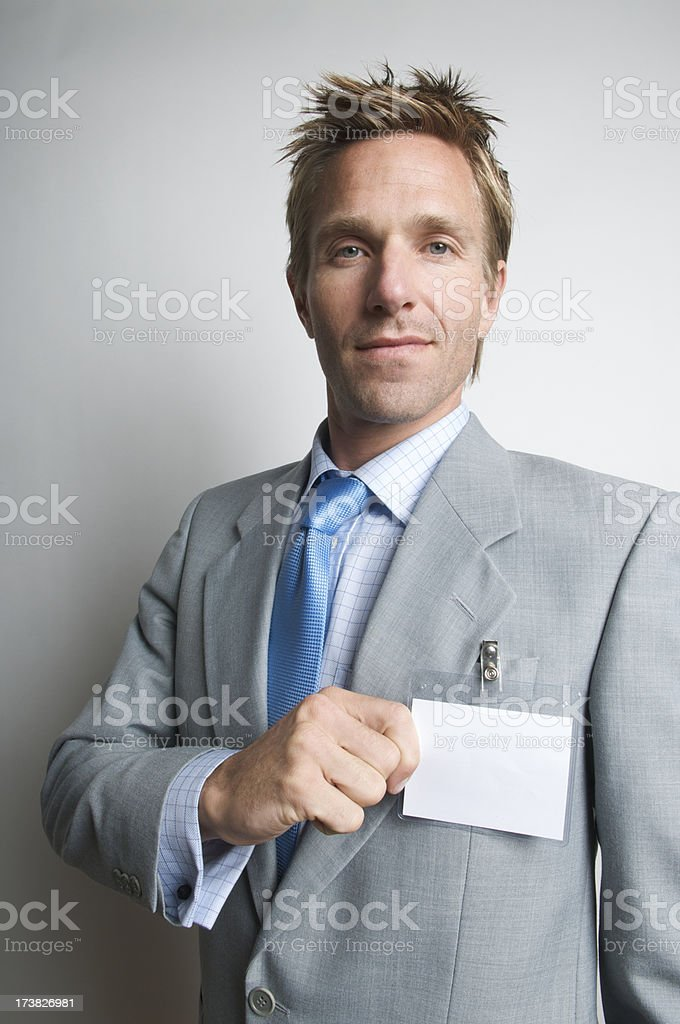 Businessman Holds Blank Name Tag Serious Expression royalty-free stock photo