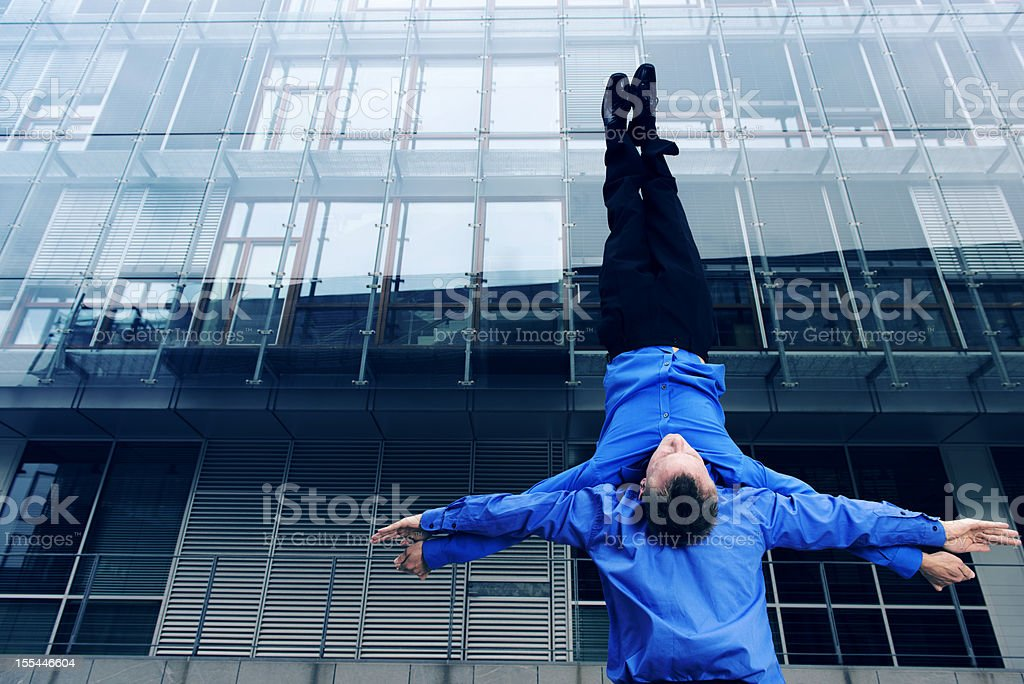 Businessman holds colleague upside down in front of office building royalty-free stock photo
