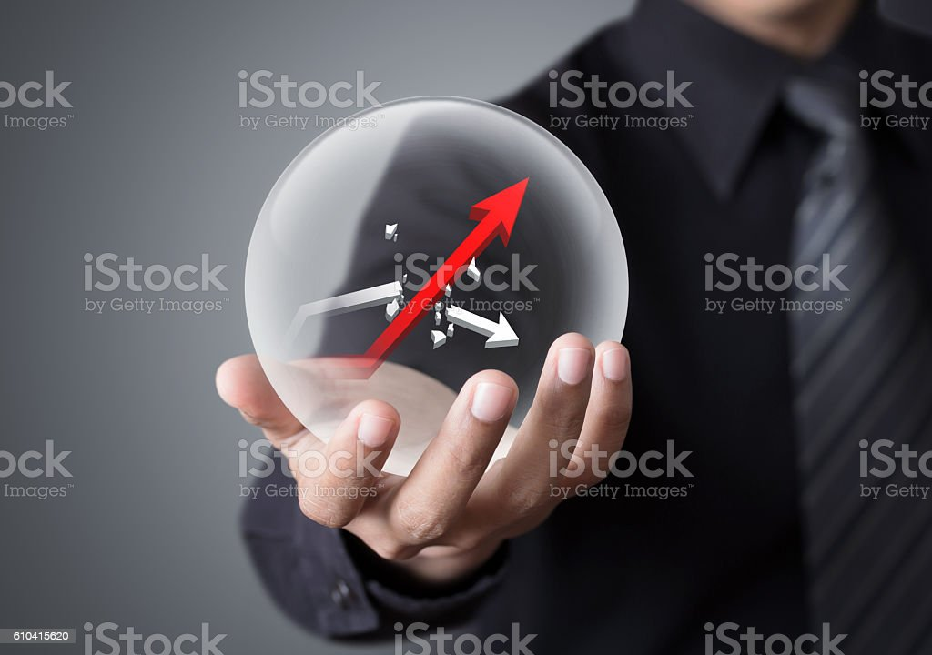 Businessman holds crystal ball with rising red graph stock photo